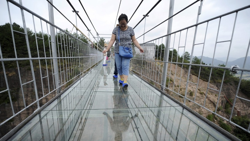 File photo - A tourist looks down as she walks on a glass suspension bridge at the Shiniuzhai National Geo-park in Pinging county, Hunan province, China, Sept. 24, 2015.