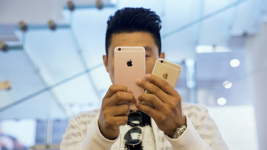 A man takes pictures as Apple iPhone 6s and 6s Plus go on sale at an Apple Store in Beijing, China Sept. 25, 2015.