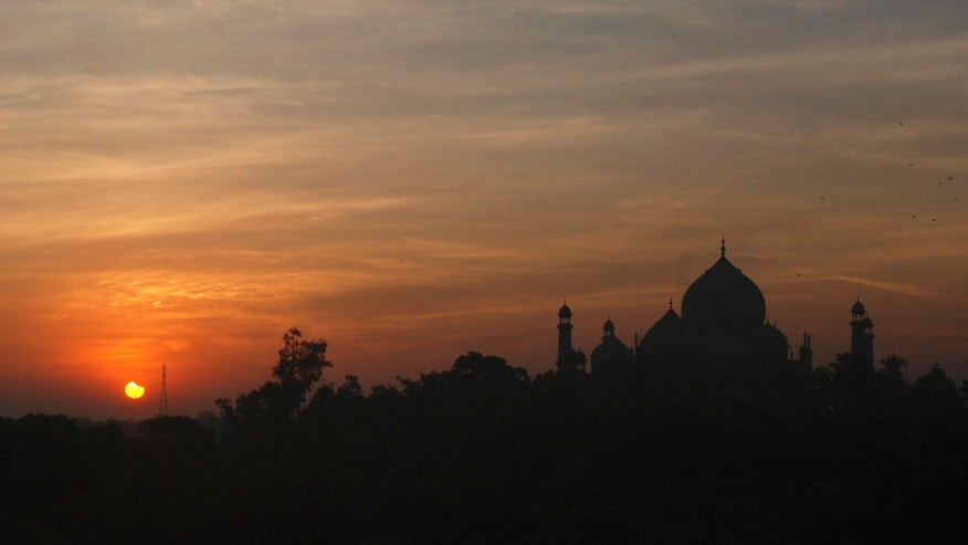 File photo - A partial solar eclipse is seen behind the Taj Mahal in the northern Indian city of Agra July 22, 2009.