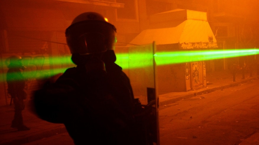 File photo - A riot policeman is aimed at with a laser light pointer during riots outside the Athens Polytechnic Dec. 14, 2008. (REUTERS/Yiorgos Karahalis)