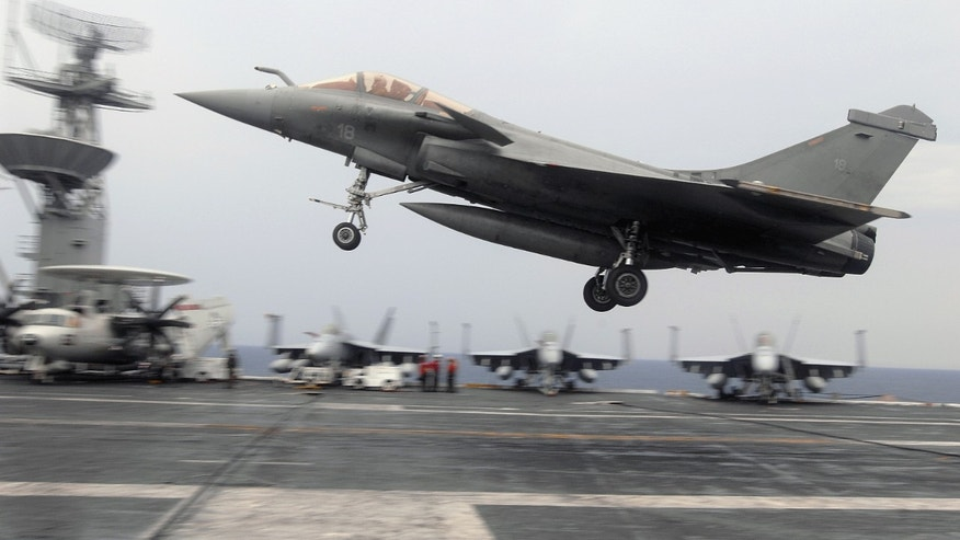 "File photo - A French F-2 Rafale fighter performs a touch-and-go during combined French and American carrier qualifications aboard the aircraft carrier USS Theodore Roosevelt (CVN 71). The Theodore Roosevelt Carrier Strike Group is participating in Joint Task Force Exercise ""Operation Brimstone"" off the Atlantic coast. (U.S. Navy photo by Mass Communication Specialist 3rd Class Sheldon Rowley/Released)"