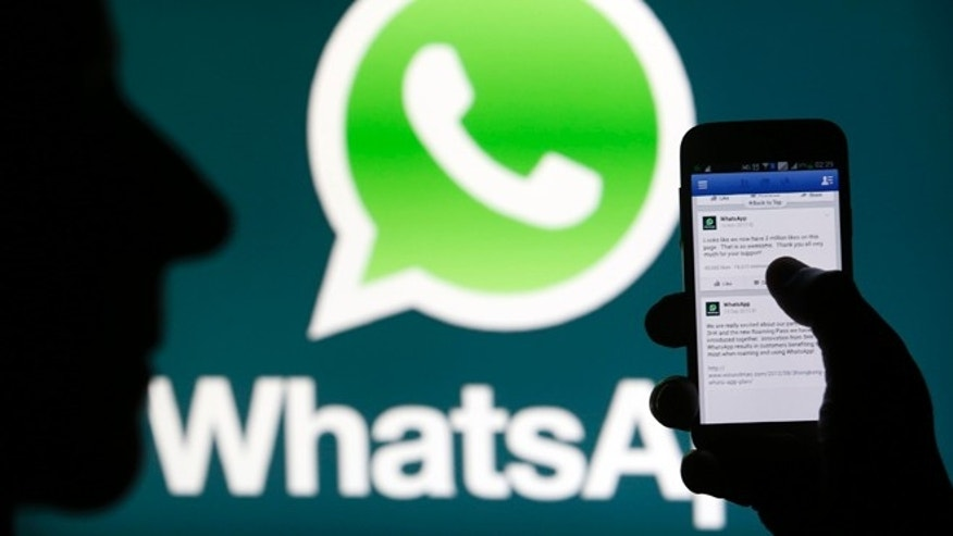 A Whatsapp App logo is seen behind a Samsung Galaxy S4 phone that is logged on to Facebook. (Reuters)