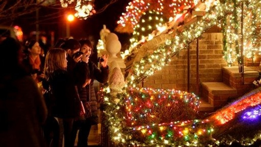 This Dec. 4, 2012, photo shows spectators viewing an elaborately decorated home for the holidays in Brooklyn, NY.