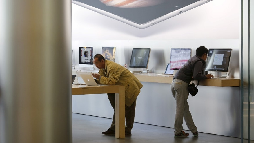 Men try apple's MacBook laptops at an apple store in Beijing. (REUTERS/Kim Kyung-Hoon)