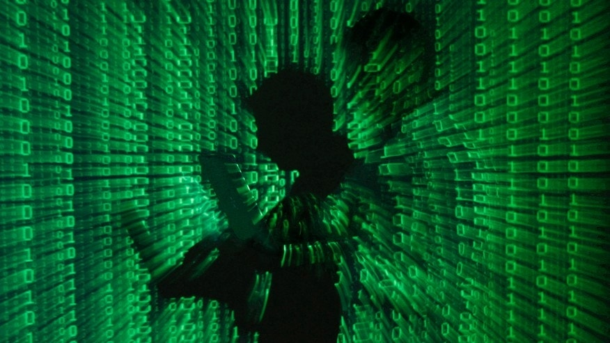 An illustration picture shows a projection of binary code on a man holding a laptop computer, in an office in Warsaw June 24, 2013. (REUTERS/Kacper Pempel)