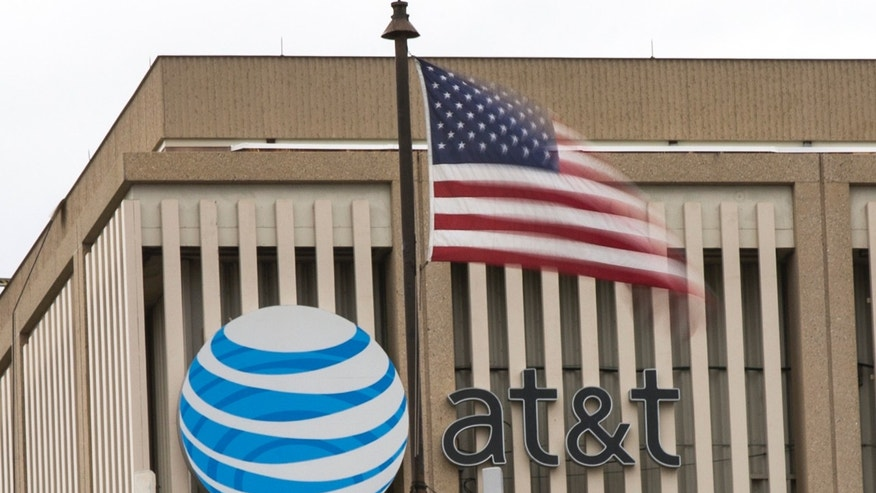 An AT&T Logo is pictured as a U.S. flag flutters in the foreground in Pasadena, California, Jan. 26, 2015. (REUTERS/Mario Anzuoni)