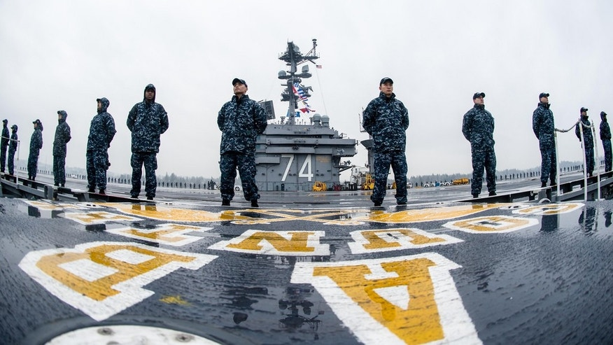 Sailors man the rails aboard USS John C. Stennis' (CVN 74) flight deck as the aircraft carrier gets underway for a deployment that will include operations in both the U.S. 3rd Fleet and U.S. 7th Fleet areas of responsibility, while also serving, along with its strike group, as the centerpiece of the Great Green Fleet, a year-long initiative highlighting the Navy's efforts to transform its energy use to increase operational capability. (U.S. Navy photo by Mass Communication Specialist 3rd Class Andre T. Richard)