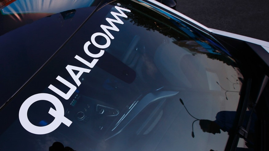 File photo - A logo of U.S. chipmaker Qualcomm is seen on the windshield of a car in Beijing Sept. 13, 2014.