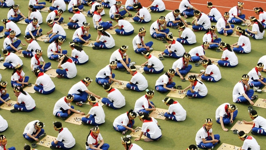 "Students play the board game ""Go"", known as ""Weiqi"" in Chinese, during a competition to mark the 100-day countdown to the opening of Beijing Olympics at a primary school in Suzhou, Jiangsu province. (REUTERS/China Daily)"