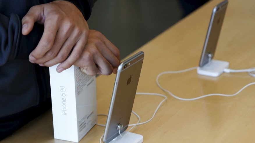 File photo - A customer holds a box of iPhone 6 at an Apple store in Beijing, Nov. 2, 2015. (REUTERS/Kim Kyung-Hoon)