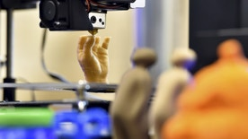 3D printed objects are displayed as an artificial hand is being printed during a 3D printing show in Brussels, Belgium, October 18, 2015. REUTERS/Eric Vidal - RTS4YHN
