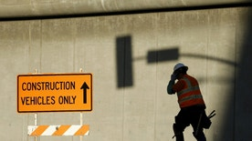 A worker talks on a mobile phone from a downtown construction site in Los Angeles, California January 29, 2016.  REUTERS/Mike Blake   - RTX24MBF