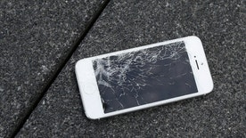FILE - This Aug. 26, 2015 photo shows an Apple iPhone with a cracked screen after a drop test from the DropBot, a robot used to measure the sustainability of a phone to dropping, at the offices of SquareTrade in San Francisco. Apple for the first time is accepting banged up iPhones as a trade-in from those wanting to upgrade.   (AP Photo/Ben Margot)