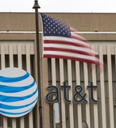 An AT&T Logo is pictured as a U.S. flag flutters in the foreground in Pasadena, California, January 26, 2015. REUTERS/Mario Anzuoni  (UNITED STATES - Tags: BUSINESS LOGO) - RTR4N29N