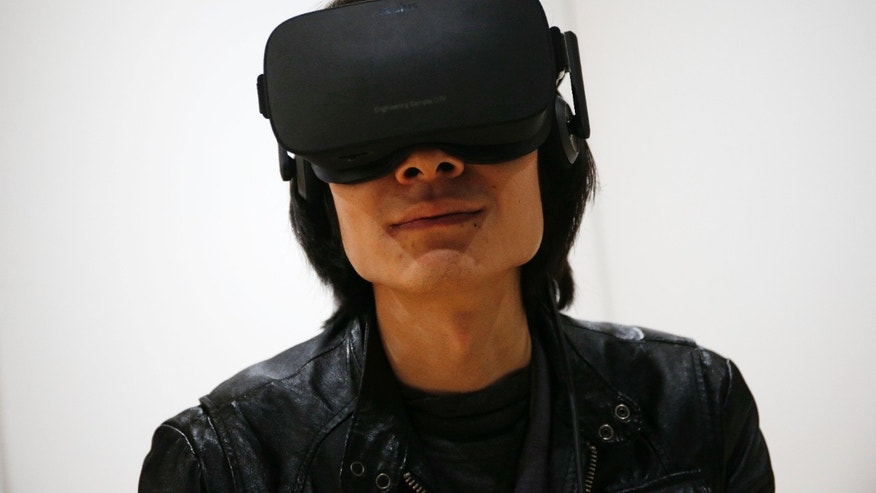 File photo - Peijun Guo wears the Oculus Rift VR headset at the Oculus booth at CES International, Wednesday, Jan. 6, 2016, in Las Vegas. (AP Photo/John Locher)