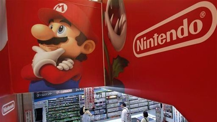 Shoppers walk under the logo of Nintendo and Super Mario characters at an electronics store in Tokyo.