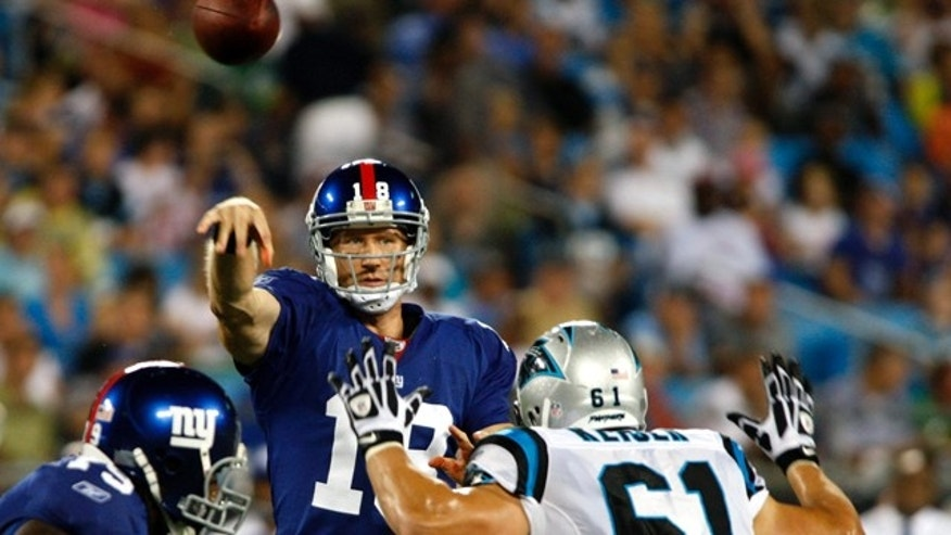 File photo - New York Giants quarterback Sage Rosenfels passes over Carolina Panthers defensive end Thomas Keiser (R) in the first half of an NFL pre-season football game in Charlotte, North Carolina Aug. 13, 2011. (REUTERS/Nell Redmond)