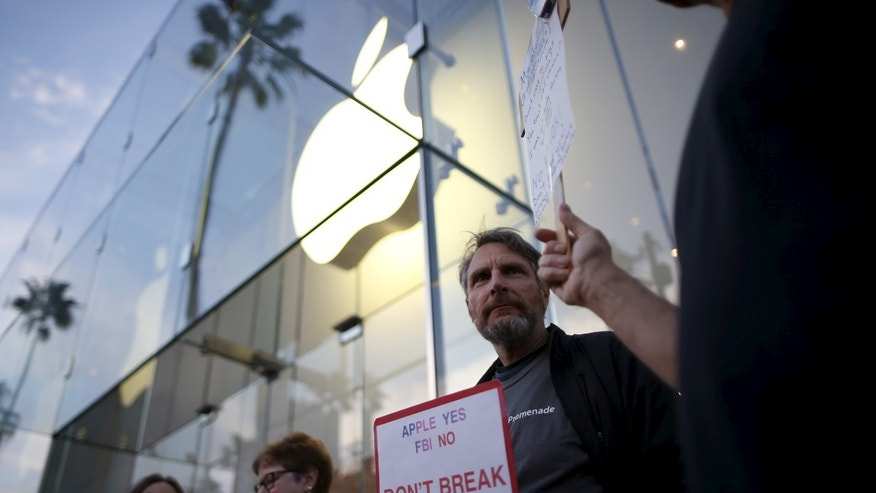 People gather at a small rally in support of Apple's refusal to help the FBI access the cell phone of a gunman involved in the killings of 14 people in San Bernardino, in Santa Monica, California, United States, February 23, 2016 (REUTERS/Lucy Nicholson).