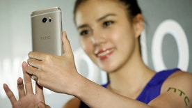 A model poses for photographs with HTC 10, an Android-based smartphone, during its launch event in Taitung, Taiwan April 12, 2016. REUTERS/Tyrone Siu - RTX29L57