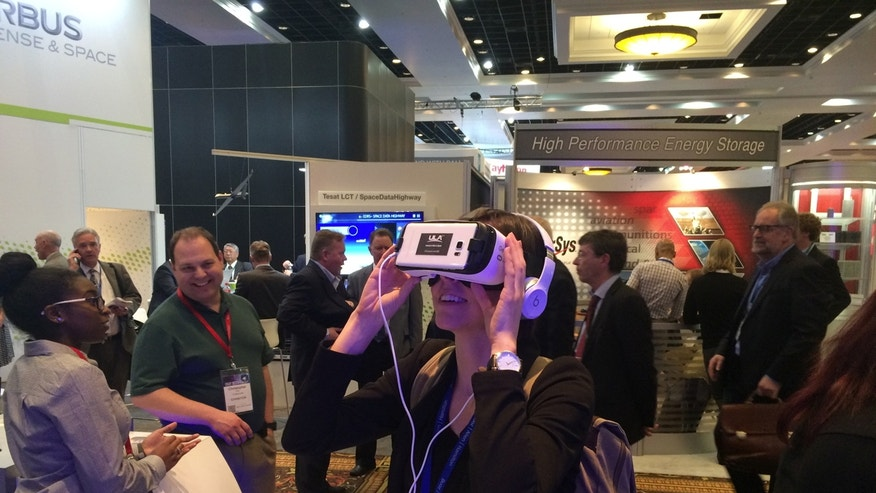 Space.com reporter Calla Cofield is thoroughly engrossed by ULA's virtual-reality view of a rocket launch.