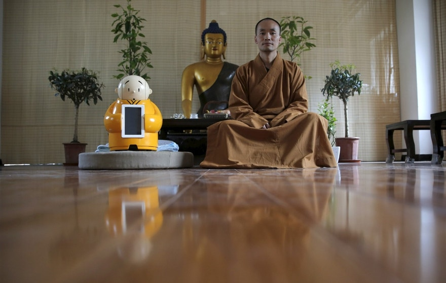 Master Xianfan sits next to robot Xian'er as he poses for photograph at Longquan Buddhist temple on the outskirts of Beijing, April 20, 2016.  REUTERS/Kim Kyung-Hoon   - RTX2B4DJ