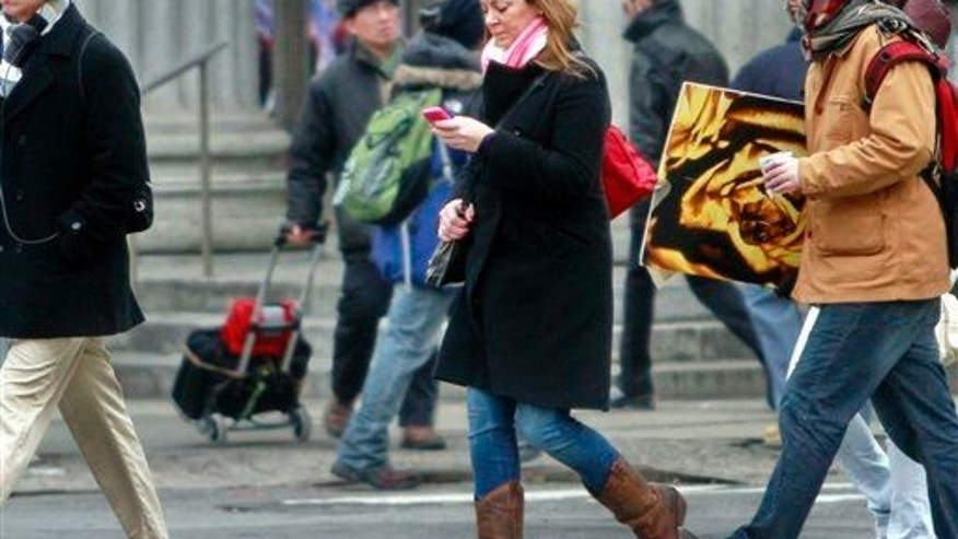 File photo of a pedestrian walking while using a phone in New York.
