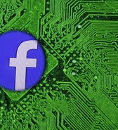 Facebook's logo is seen through a magnifier in front of a displayed PC motherboard, in this illustration taken April 11, 2016. REUTERS/Dado Ruvic/Illustration - RTX29IF2