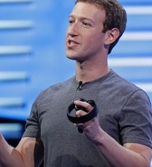 "Facebook CEO Mark Zuckerberg holds a pair of virtual reality handsets during the keynote address at the F8 Facebook Developer Conference Tuesday, April 12, 2016, in San Francisco.  Zuckerberg said Facebook is releasing new tools that businesses can use to build ""chatbots,"" or programs that can talk to customers in conversational language.  (AP Photo/Eric Risberg)"