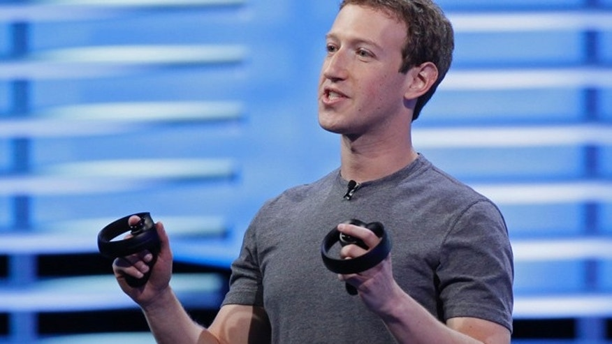 Facebook's Mark Zuckerberg holds a pair of virtual reality handsets in San Francisco