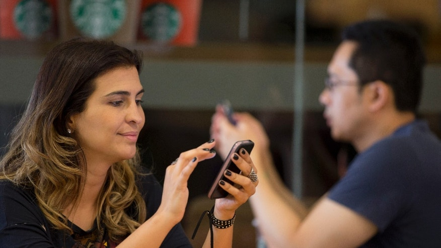File photo - A woman checks her cell phone at a coffee shop in Sao Paulo, Brazil, Thursday, Dec. 17, 2015. (AP Photo/Andre Penner)