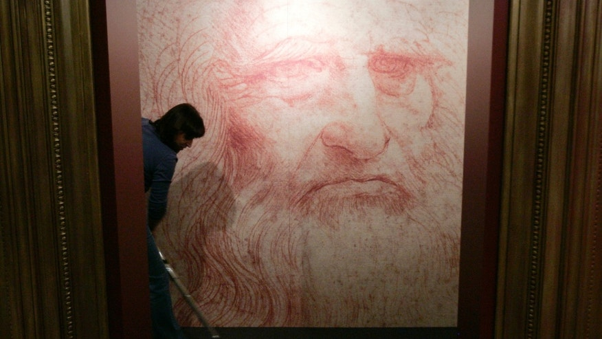"A cleaner vacuums in front of a Leonardo da Vinci self-portrait drawn around 1515 or 1516, during the inauguration of the exhibition ""Leonardo da Vinci, the European Genius"" in Brussels, August 17, 2007. (REUTERS/Francois Lenoir)"