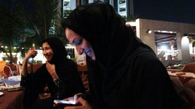 In this Nov. 11, 2010, file photo, Saudi women with cellphones smoke tobacco and drink coffee in Jeddah, Saudi Arabia.