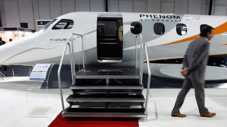 "A man walks past a replica of Embraer's Phenom 300 jet at the ""Extravaganza 2008 Show"" in Mumbai February 23, 2008."