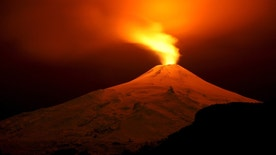 The Villarrica Volcano is seen at night from Pucon town, Chile, July 11, 2015. Villarrica, located near the popular tourist resort of Pucon, is among the most active volcanoes in South America. Picture taken July 11, 2015. REUTERS/Cristobal Saavedra - RTX1K2TI