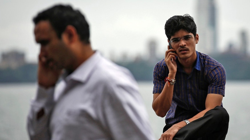 File photo - men speak on their mobile phones on a seafront in Mumbai