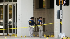 FBI investigators look over the crime scene in Dallas, Texas, U.S. July 8, 2016 following a Thursday night shooting incident that killed five police officers.  REUTERS/Carlo Allegri - RTX2KDZO