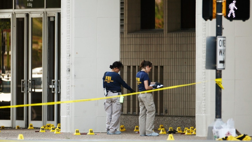 FBI investigators look over the crime scene in Dallas, Texas, U.S. July 8, 2016 following a Thursday night shooting incident that killed five police officers. (REUTERS/Carlo Allegri)