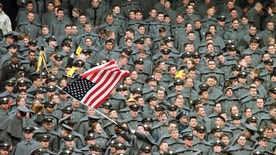 A lone West Point Cadet waves the American flag amid a sea of fellow Cadets as they watch Navy take a commanding lead in the first half of the Army-Navy game, December 6 at Giants Stadium in East Rutherford.