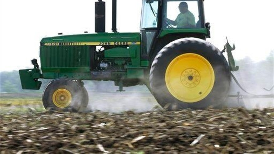 In this April 2, 2012 photo, Derek Long uses a John Deere tractor in preparation for planting corn in Loami, Ill. A slowing global economy and the effects of a prolonged U.S. drought caught up to Deere & Co. as its net income rose 11% but fell well short of Wall Street's expectations.