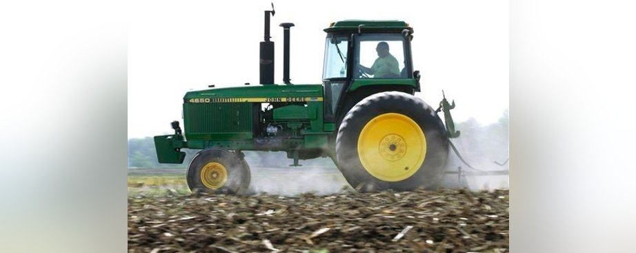 In this April 2, 2012 photo, Derek Long uses a John Deere tractor to disk and cultivate a field in preparation for planting corn in Loami, Ill. A slowing global economy and the effects of a prolonged U.S. drought caught up to Deere & Co. in its fiscal third quarter, as its net income rose 11 percent but fell well short of Wall Street's expectations. (AP Photo/Seth Perlman)
