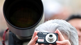 A faithful takes a picture next to a professional photographer's lens to Pope Benedict XVI as he leads his Angelus prayer from the window of his private apartments in Saint Peter Square at the Vatican November 16, 2008.     REUTERS/Max Rossi    (VATICAN) - RTXANJW