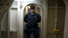 A crew member stands guard in a doorway as U.S. Defense Secretary Ash Carter tours the USS Eisenhower off the coast of Virginia, in the Atlantic Ocean, December 10, 2015. Carter visited the carrier with Indian Defence Minister Manohar Parrikar to demonstrate U.S. Navy aircraft carrier flight operations. REUTERS/Mark Wilson/Pool - RTX1Y6HI