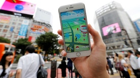 """A man poses with his mobile phone displaying the augmented reality mobile game """"Pokemon Go"""" by Nintendo in front of a busy crossing in Shibuya district in Tokyo, Japan, July 22, 2016. REUTERS/Toru Hanai - RTSJ5OT"""