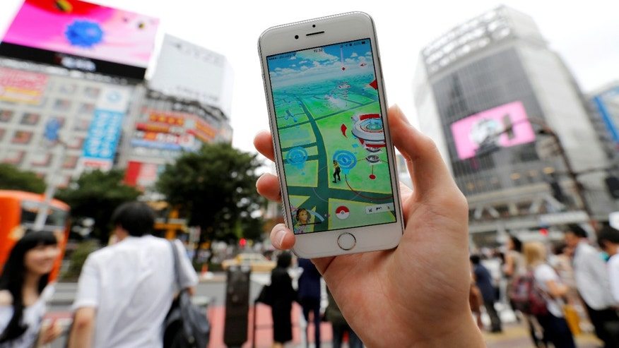 "File photo - A man poses with his mobile phone displaying the augmented reality mobile game ""Pokemon Go"" by Nintendo in front of a busy crossing in Shibuya district in Tokyo, Japan, July 22, 2016. (REUTERS/Toru Hanai)"