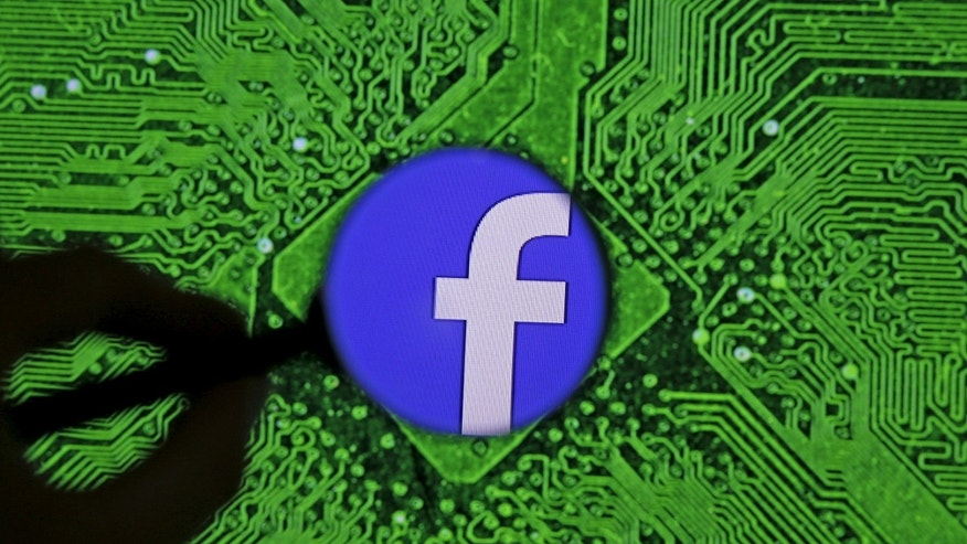 Facebook's logo is seen through a magnifier in front of a displayed PC motherboard, in this illustration taken April 11, 2016.