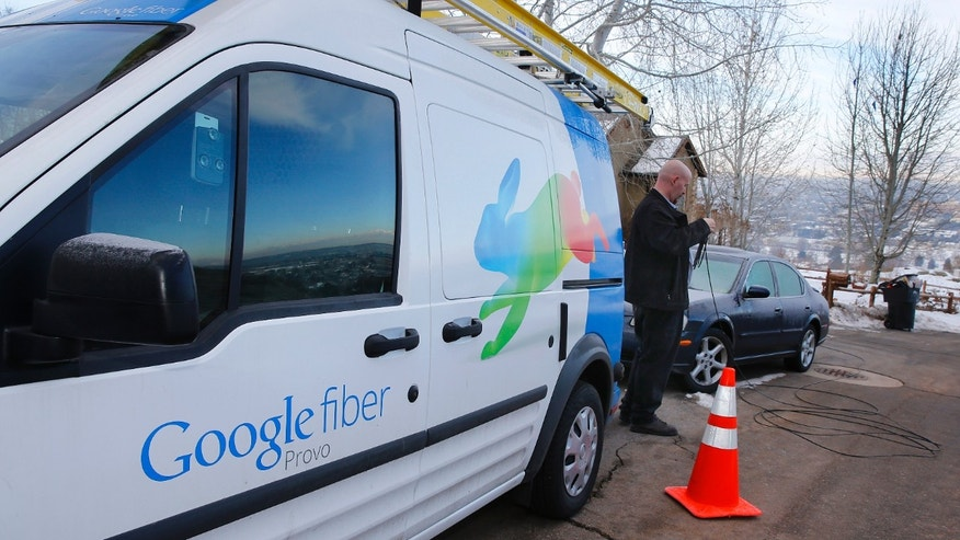 A technician gets cabling out of his truck to install Google Fiber in a residential home in Provo, Utah, January 2, 2014.