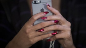 A model's nails are seen as she uses her cell phone backstage before the Betsey Johnson Spring/Summer 2016 collection presentation during New York Fashion Week in New York, September 11, 2015. REUTERS/Andrew Kelly - RTSP7K