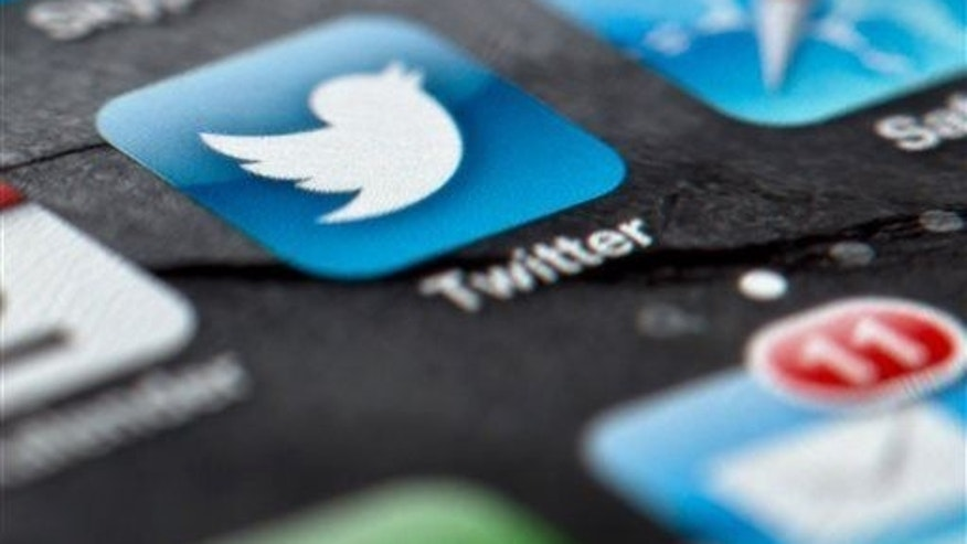 FILE - In this Feb. 2, 2013, file photo, a smartphone display shows the Twitter logo in Berlin, Germany