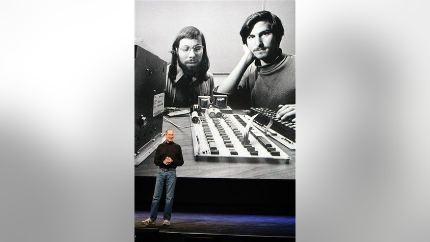 In this 2010 image, Steve Jobs stands in front of an old photo of himself and Steve Wozniak.