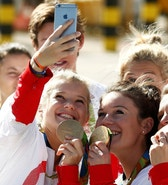 Team GB athletes pose with their medals for selfies as they return home from the 2016 Rio Olympics, at Heathrow Airport in London, Britain August 23, 2016. REUTERS/Peter Nicholls - RTX2MNRC